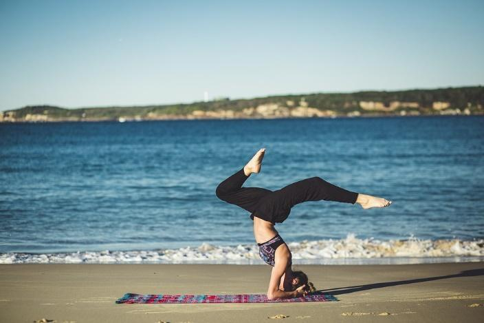 Woman-Doing-Yoga-On-Beach