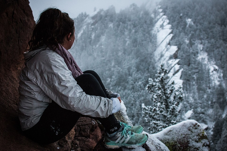 woman staring at snowy mountains